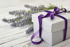 Gift box with violet ribbon. And bouquet of lavender on wooden background Stock Images