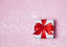 Gift box vith red bow and glitter sparkles on pink background. st. Valentine`s day concept