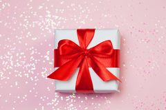Gift box vith red bow and glitter sparkles on pink background. st. Valentine`s day concept.  Stock Photos