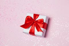 Gift box vith red bow and glitter sparkles on pink background. st. Valentine`s day concept.  Stock Photo
