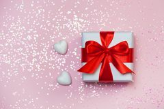Gift box vith red bow and glitter sparkles on pink background. st. Valentine`s day concept.  Royalty Free Stock Image