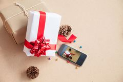 The gift box was placed with decorations items of Christmas day. Concept that was changed by the era. Until the modern era, giving gifts is easy through smart Royalty Free Stock Photography
