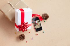 The gift box was placed with decorations items of Christmas day. Concept that was changed by the era. Until the modern era, giving gifts is easy through smart Royalty Free Stock Image