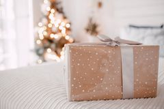 Gift box on a white bed. Christmas tree at background. Gift box on a white bed. Christmas tree and window with the morning light at background, silver ribbon and Stock Images