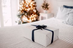 Gift box on a white bed close up. Christmas tree and window with the morning light at background. Blue ribbon and white paper Royalty Free Stock Photos