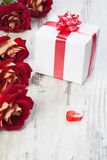 Gift box on a white board with red roses Stock Images