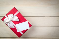 Gift box with blank business name card. Gift box with white bow and blank name card on wooden board background Royalty Free Stock Image