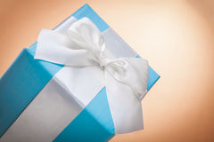 Gift box with white bow on light brown backgrond with copyspace Royalty Free Stock Image