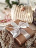 Gift box with white bowknot surrounded knitted cloths, lights, rose in soft focus. Gift box with white bowknot surrounded knitted cloths, lights, rose stock photos