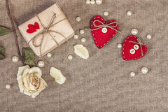 Gift box with a white dry rose and two red hearts on sacking, co Royalty Free Stock Images
