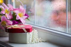 Open gift box with white pearl necklace near near window with raindrops in the daylight. Gift box with white pearl necklace near near window with raindrops in Stock Photos