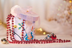 Gift box whith a red bead and christmas balls. Royalty Free Stock Image