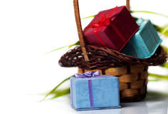 Gift boxes and wicker basket. Colourful gift boxes in wicker basket Royalty Free Stock Image