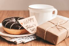 Free Gift Box With A Tag, Cup Of Coffee Or Tea And Chocolate Donut. Father`s Day Or Birthday Concept Royalty Free Stock Photo - 182744035
