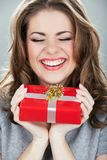 Gift box woman hold against gray background. Close up portrait of young smiling model stock image