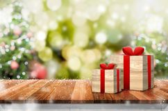 Gift box on wood plank table top with abstract blur christmas tr royalty free stock image