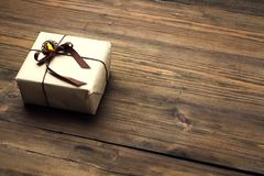 Gift Box on Wood Table, Wrapped Vintage Paper Present With Bow. Lying on Brown Wooden Planks Royalty Free Stock Image