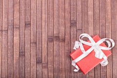Gift box on a wooden background. Gift box placed on a bamboo made background Stock Photos
