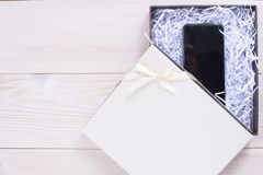 Gift box on wooden light background. Mobile phone stock photo