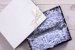 Gift box on wooden light background. Wrench. Unexpected gift royalty free stock photos