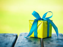 Gift box on wooden table. On natural sunny background Stock Photos