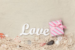 Gift box and word Love with net and shells Royalty Free Stock Photography