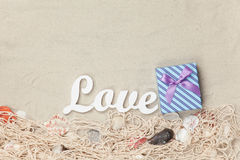 Gift box and word Love with net and shells Stock Photo