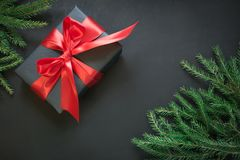 Gift box wrapped in black paper with red ribbon in female hand on black surface. Top view. Christmas card. Royalty Free Stock Photos