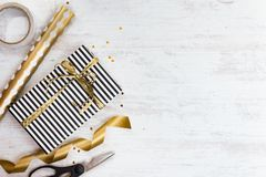 Gift box wrapped in black and white striped paper with golden bow and wrapping materials on a white wood old background. Empty spa Royalty Free Stock Photography