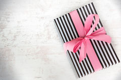 Gift box wrapped in black and white striped paper with pink ribbon on a white wood old background Stock Photo