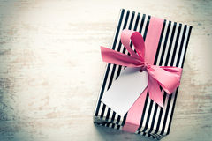 Gift box wrapped in black and white striped paper with pink ribbon on a white wood old background. Empty note tied over. Vintage s Stock Image
