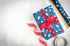 Gift box wrapped in blue dotted paper with red ribbon on a white wood old background.Wrapping materials scattered over the table. Royalty Free Stock Image