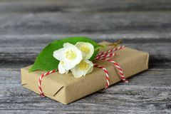 Gift wrapped in brown paper decorated with jasmine flower. Gift box wrapped in brown paper decorated with jasmine flower stock image