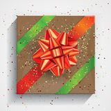 Gift box wrapped on brown wrinkled paper with red bow Stock Photography