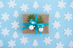 Gift box wrapped of craft paper, blue ribbon and decorated fir branches and silver Christmas balls on the blue background. Gift box wrapped of craft paper, blue royalty free stock image