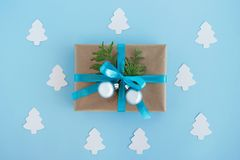 Gift box wrapped of craft paper, blue ribbon and decorated fir branches and silver Christmas balls on the blue background. Gift box wrapped of craft paper, blue royalty free stock photography