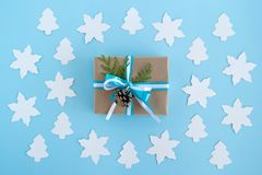 Gift box wrapped of craft paper, blue and white ribbons and decorated fir branches and pinecone on the blue background. Stock Photo