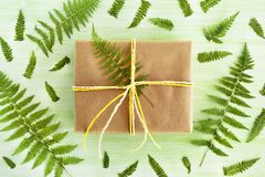 Gift box wrapped of craft paper and white and yellow ribbon on a green wooden background decorated of fern leaves. Gift box wrapped of craft paper and white and Stock Photo