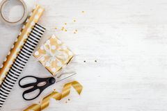 Gift box wrapped in golden dotted paper and wrapping materials on a white wood old background. Empty space. Royalty Free Stock Photos