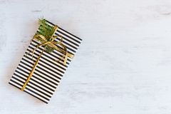 Free Gift Box Wrapped In Black And White Striped Paper With Golden Ribbon And Fir Branch On A White Wooden Background. Christmas Concep Royalty Free Stock Photos - 101072998