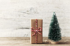 Free Gift Box Wrapped In Kraft Paper And Little Decorative Fir Tree On Wooden Rustic Background. Christmas And New Year Concept. Royalty Free Stock Photos - 77851248
