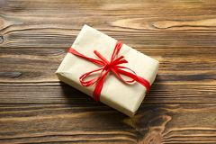 Gift box wrapped in kraft paper and red ribbon on wooden backgro stock photos