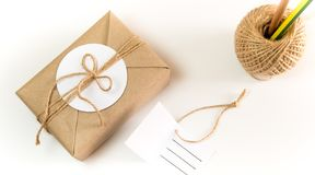 Gift box wrapped in kraft paper and rustic hemp as natural rusti. Brown gift box wrapped in kraft paper and rustic hemp cord spool as natural rustic style with royalty free stock image