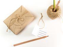 Gift box wrapped in kraft paper and rustic hemp as natural rusti. Brown gift box wrapped in kraft paper and rustic hemp cord spool as natural rustic style with royalty free stock images