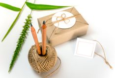 Gift box wrapped in kraft paper and rustic hemp as natural rustic style. Brown gift box wrapped in kraft paper and rustic hemp cord spool as natural rustic style royalty free stock photography