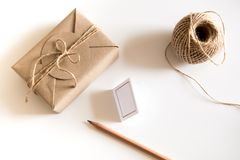 Gift box wrapped in kraft paper and rustic hemp as natural rustic style. Brown gift box wrapped in kraft paper and rustic hemp cord spool as natural rustic style stock images