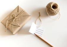 Gift box wrapped in kraft paper and rustic hemp as natural rustic style. Brown gift box wrapped in kraft paper and rustic hemp cord spool as natural rustic style royalty free stock image