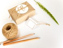 Gift box wrapped in kraft paper and rustic hemp as natural rustic style. Brown gift box wrapped in kraft paper and rustic hemp cord spool as natural rustic style stock photo