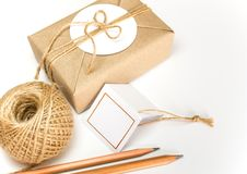 Gift box wrapped in kraft paper and rustic hemp as natural rustic style. Brown gift box wrapped in kraft paper and rustic hemp cord spool as natural rustic style royalty free stock photo
