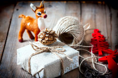 Gift box wrapped linen cloth and decorated with  cord, jute, christmas decoration on brown vintage wooden boards Stock Images